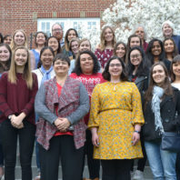 Two dozen members of the Society of Women Engineers pose for a group photo on stairs outside a building.