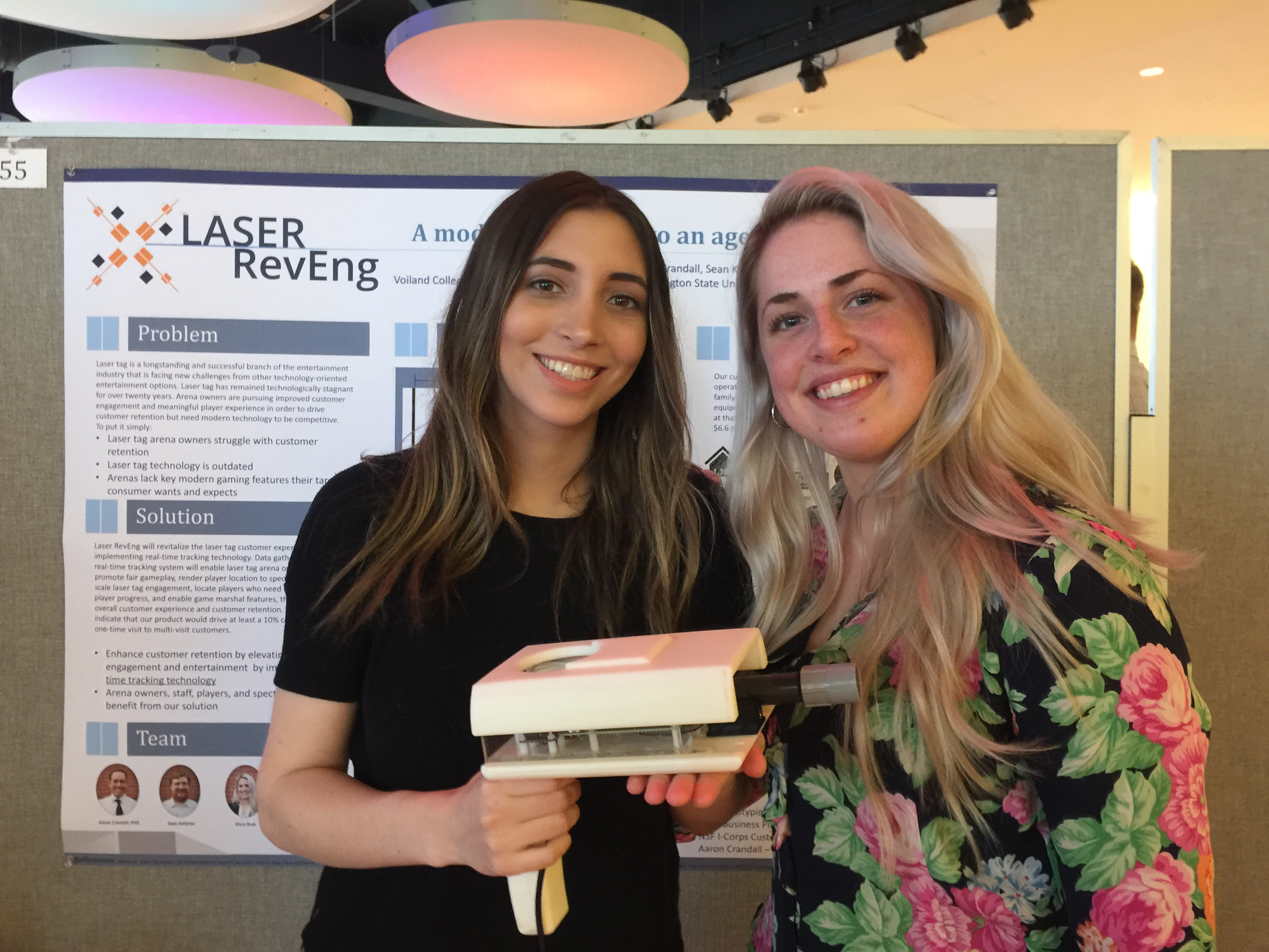 Kiera Rust standing next to Samantha Grindrod who is holding a prototype of their laser tag blaster.