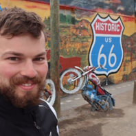 Florian Baertsch next to a Route 66 mural and motorcycle sculpture.