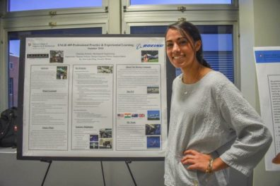 Christina poses next to a poster of her ENGR 489 presentation.