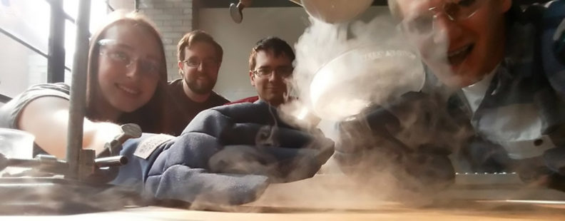 Jordan Raymond and three colleagues wearing safety glasses and gloves while magnetizing liquid air.