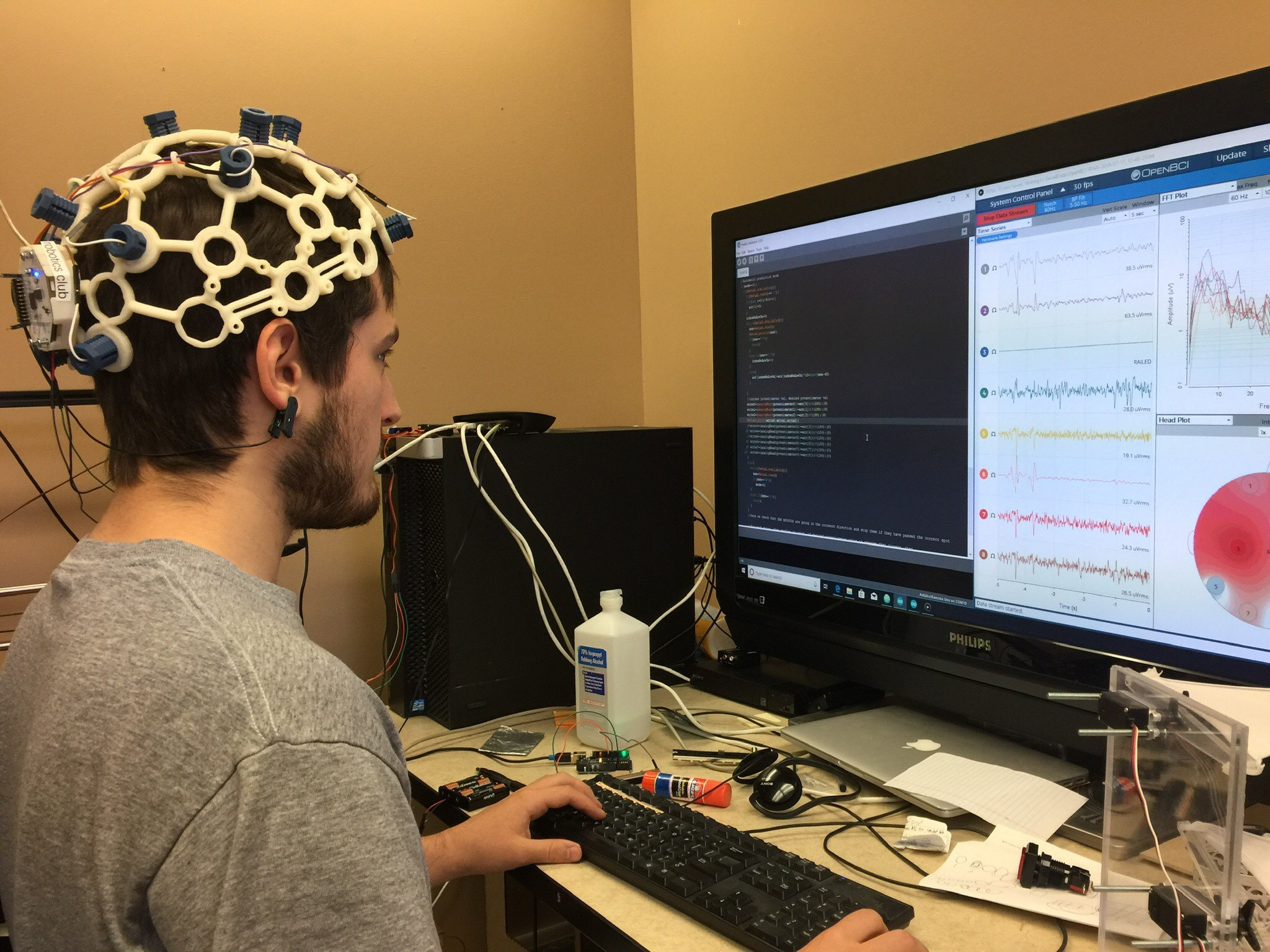 Alex Trevithick sits at a computer, wearing a helmet-like brain-computer interface.