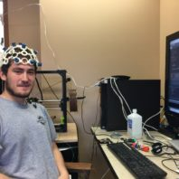 Alex Trevithick sits at a computer, wearing a helmet-like brain-computer interface, smiling at the camera.