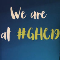 Two students pose in front of a backdrop with the text We are at #GHC19.
