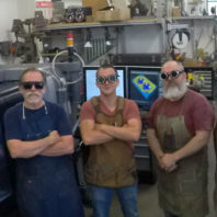 Four engineering shop workers wearing safety goggles and aprons. From left to right Miles Pepper, Eric Barrow, Wilson Boots, and Gary Held.
