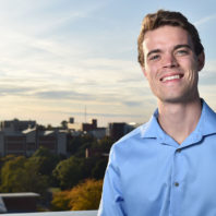 Closeup of Kristian Gubsch against a backdrop of the Washington State University Pullman campus.