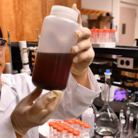 Xianming Shi holding a bottle of deicer in his lab.