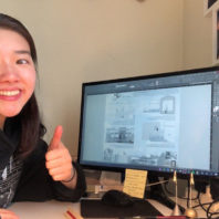 Nicole Liu showing thumbs up at her computer desk.
