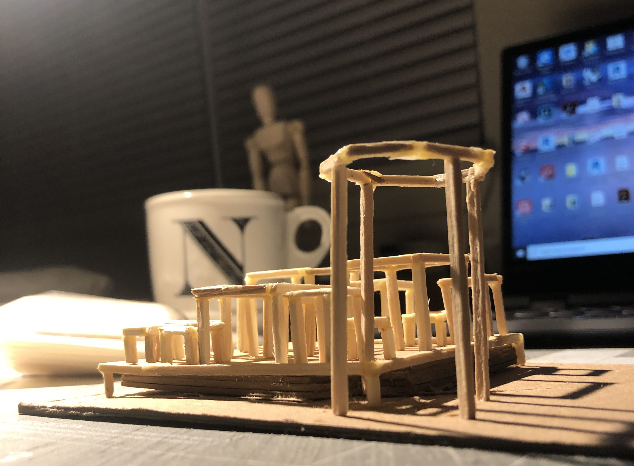 Architecture model with a coffee mug and a computer screen in the background.