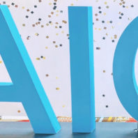 "Neeru Chaudhary seated in front of ""AIO"" block letters."