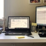 A laptop, monitor, and books on a desk.