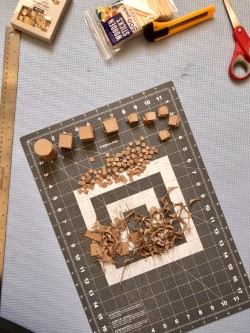 Wooden model-making pieces on a cutting mat with scissors and a utility knife.