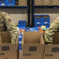 Two National Guard members fill boxes with food.