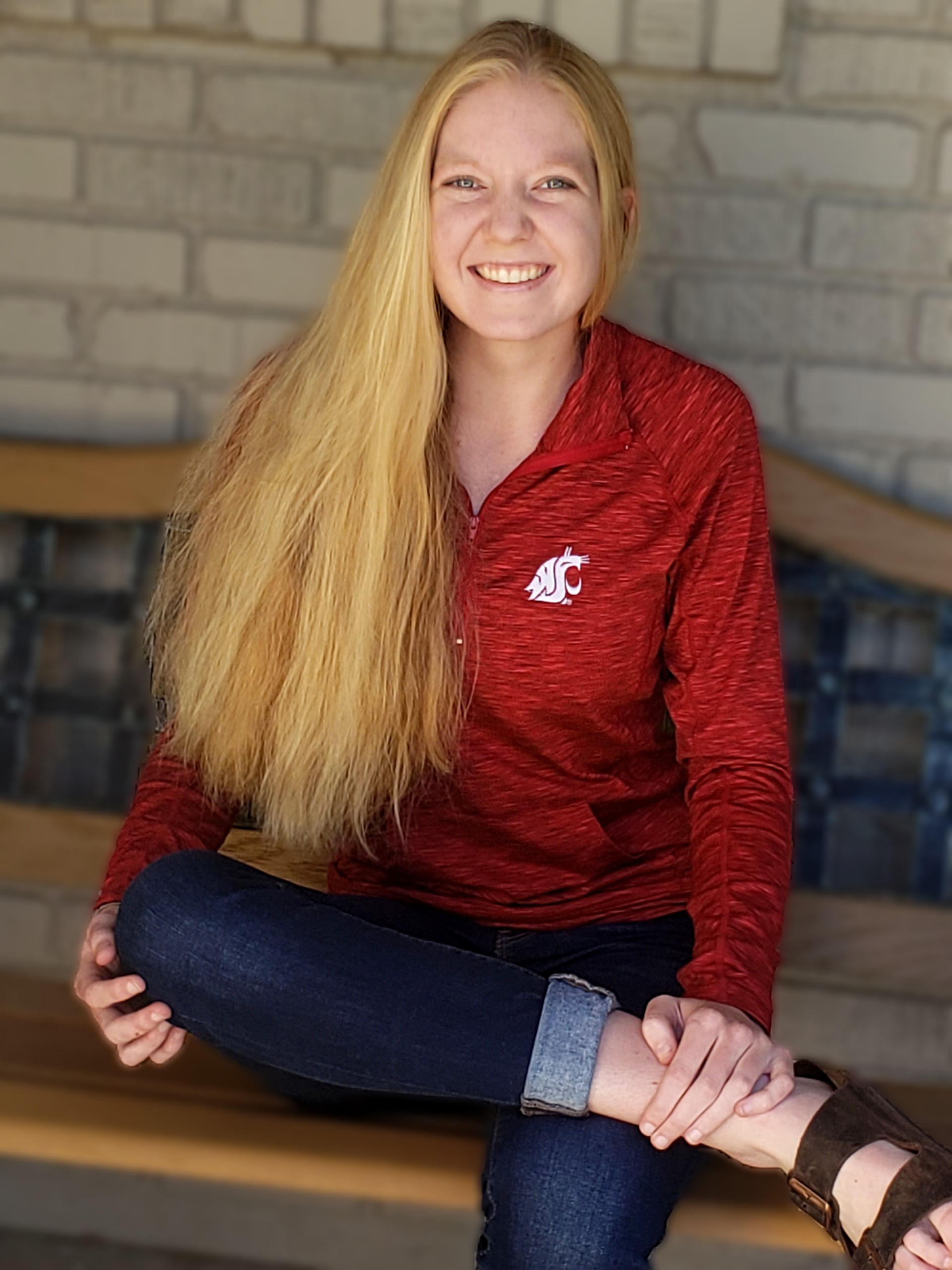 Jessica Erickson seated on a bench and wearing WSU Cougar spirit gear.