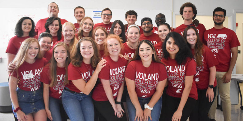 Voiland College ambassadors wearing crimson t-shirts pose in four rows for a group picture.