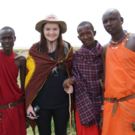 Thayer stands with three Maasai tribe members.