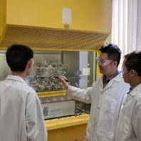 Professor Hongfei Lin with two of his students working in the lab
