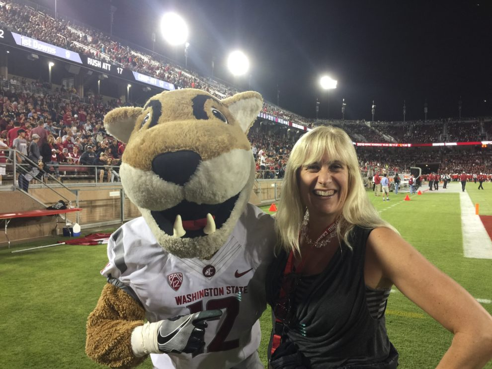 Laurie Yoler poses with WSU mascot Butch T. Cougar on the WSU football field.