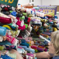 women reach into stacks of colorful rolled fabric