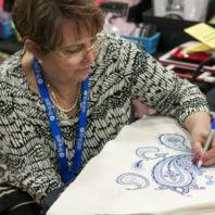 Woman draws blue paisley pattern on white fabric