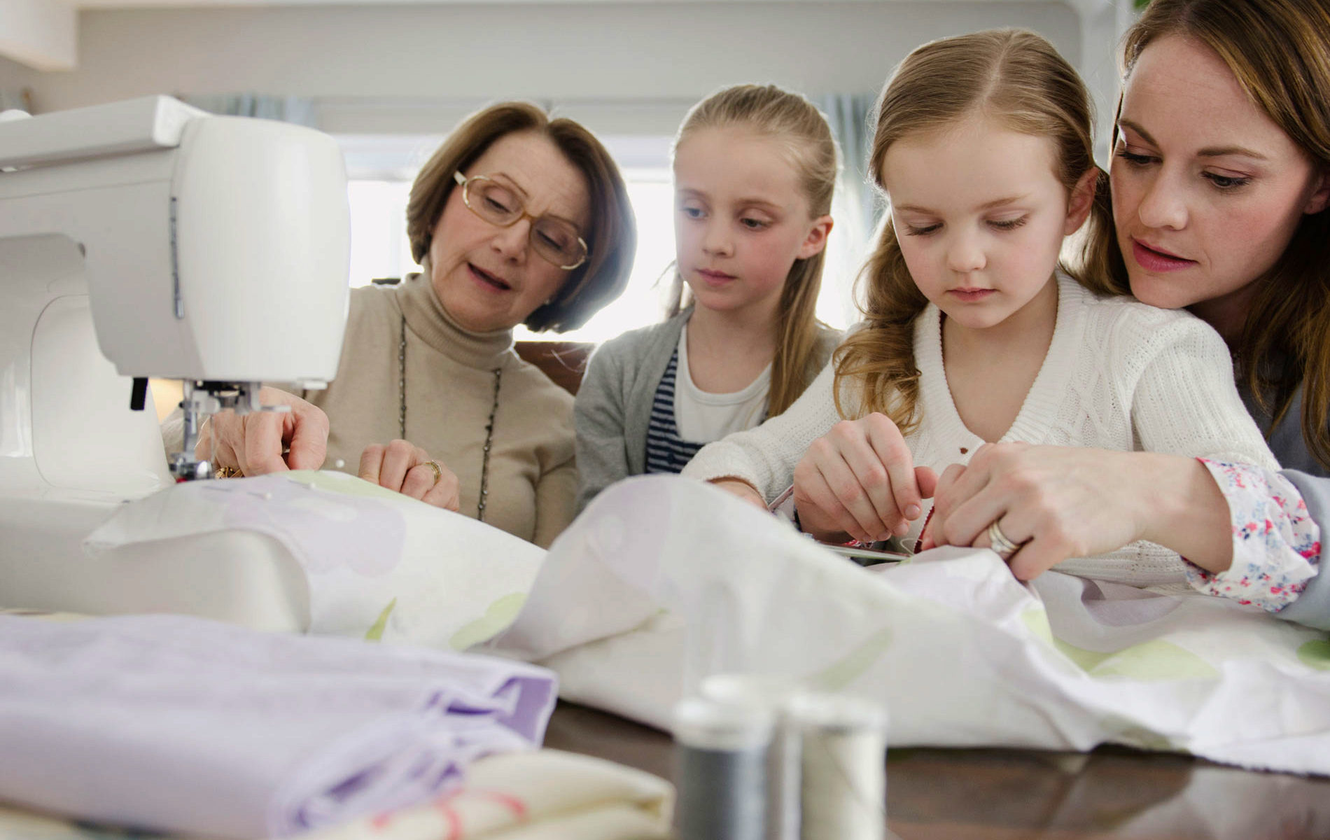 Older women and young girls sew together