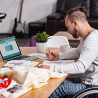 man in wheel chair studies fashion drawings at table with laptop, fabric, sewing materials