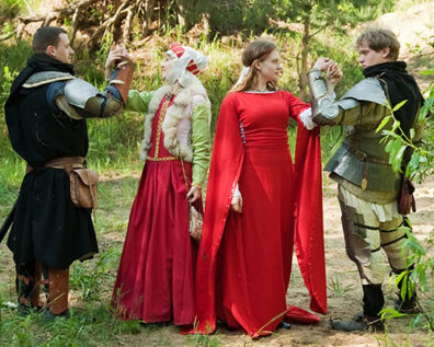 Two couples in medieval costume clasp arms