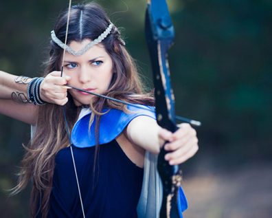 Young woman in blue costume readies to shoot arrow from bow