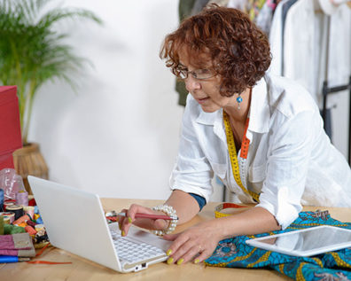 A middle-aged dressmaker consults a laptop