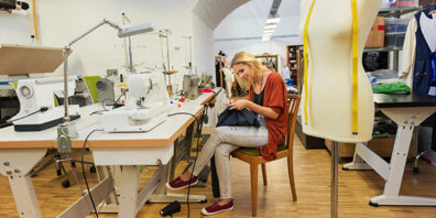 Woman hand sews in crowded sewing room