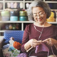 woman smiles, listens to ear buds, as she knits heavy pink yarn into garter stitch