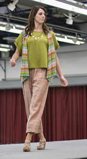 Woman models clothes on style show walkway