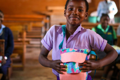 An African girl with a purse for Sew Powerful