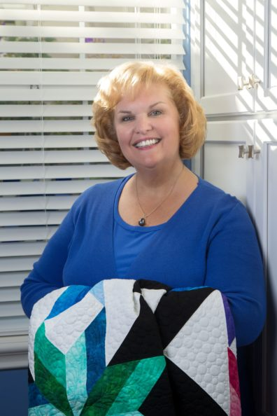 Kimberly Einmo in a sunny room with a quilt.