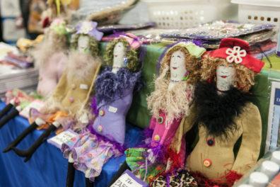 A vendor shows off dolls.
