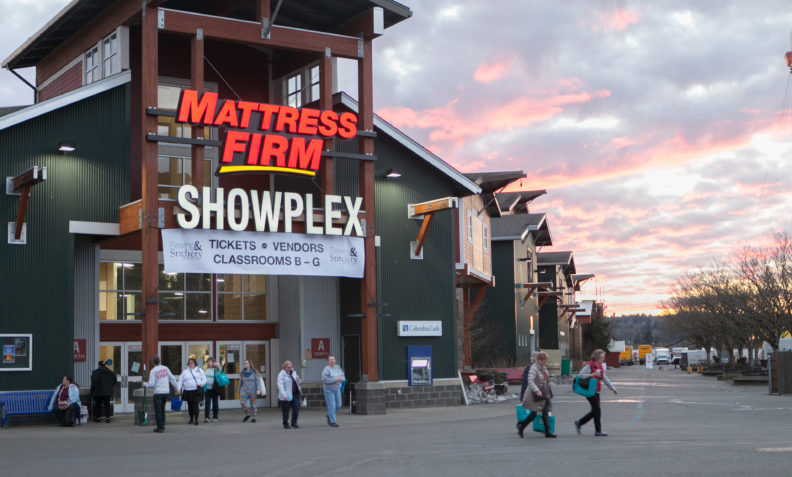 Shoppers exit the Showplex Building at sunset.
