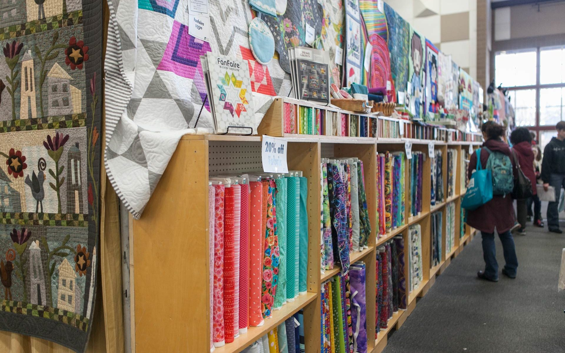 Shoppers browse long row of shelves full of colorful fabrics.