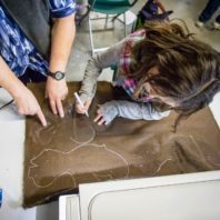 Shot from above, a young girl traces a pattern onto faux fur