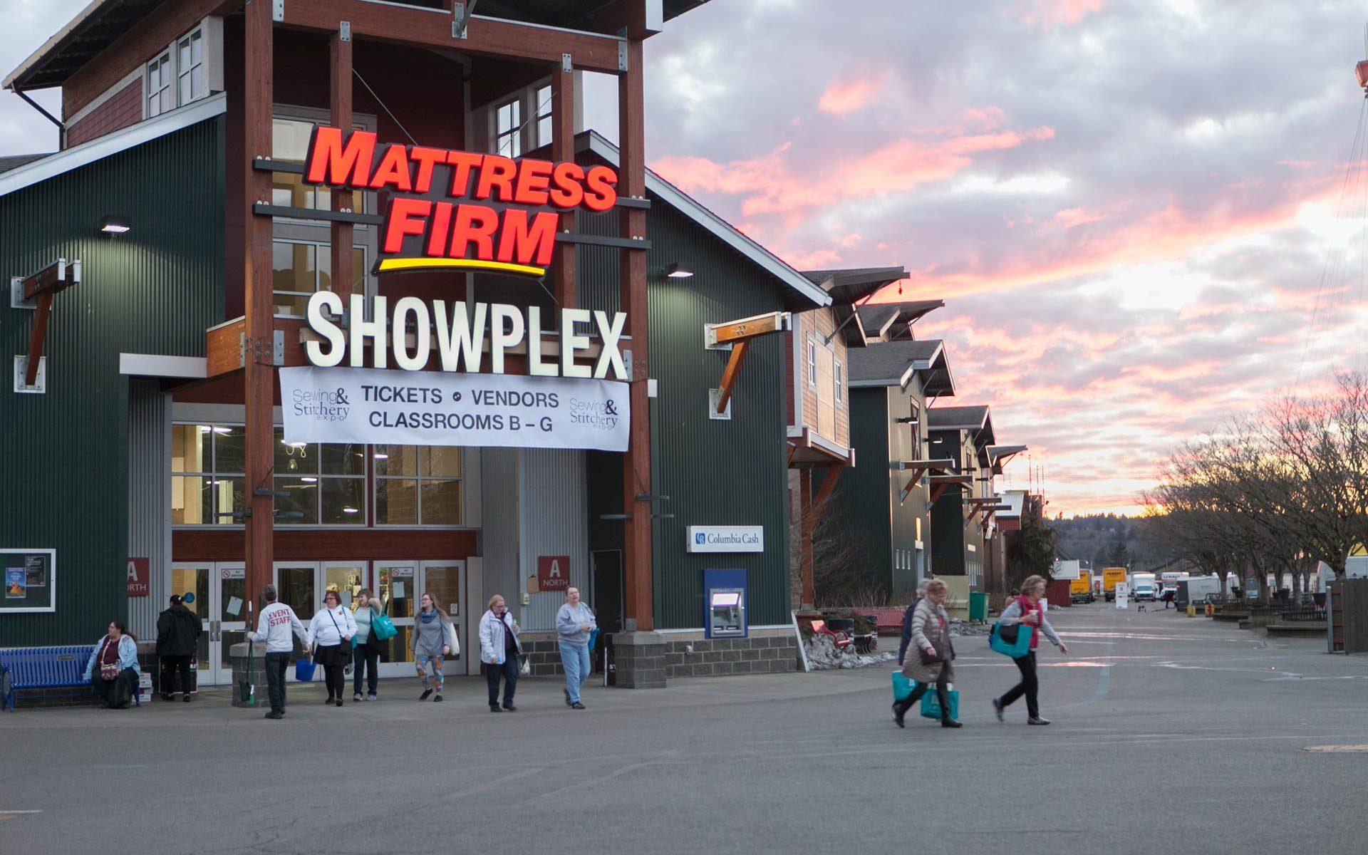Shoppers exit the Showplex Building at sunset.