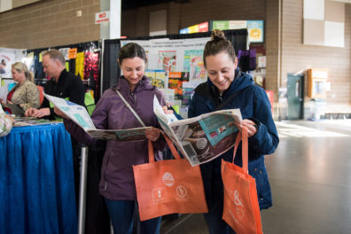 Women browse the newspaper handout at the 2020 Expo.