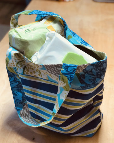 A Step By Step tote bag filled with items for a new family.