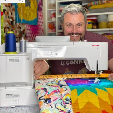 Mister Domestic, or Mathew Boudreaux, works on a colorful quilt at a sewing machine.