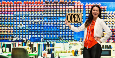 "A woman stands in front of a wall of thread with an ""Open"" sign"