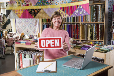 "A woman holds an ""open"" sign in a fabric shop."