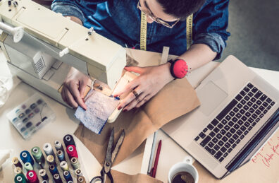 A woman works on a sewing machine with her laptop.