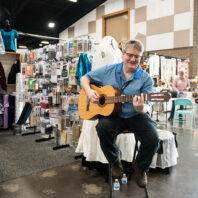 A vendor plays guitar during the 2020 Sewing & Stitchery Expo.