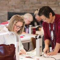A teacher helps a student during the 2020 Sewing & Stitchery Expo.