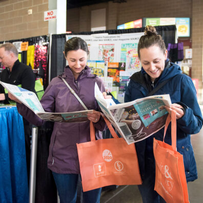 Two women read the Expo on-site newspaper while holding orange Expo bags.