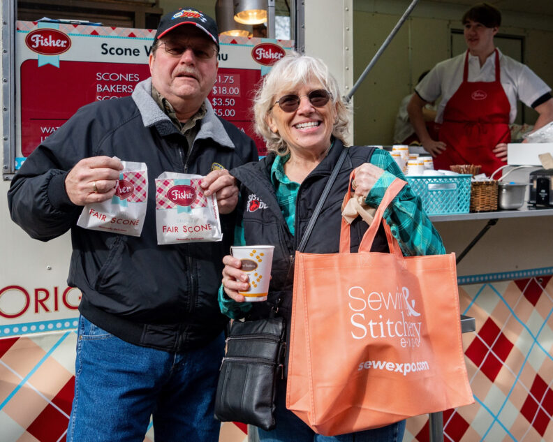 Older man and woman showing off scones and Sew Expo bag.