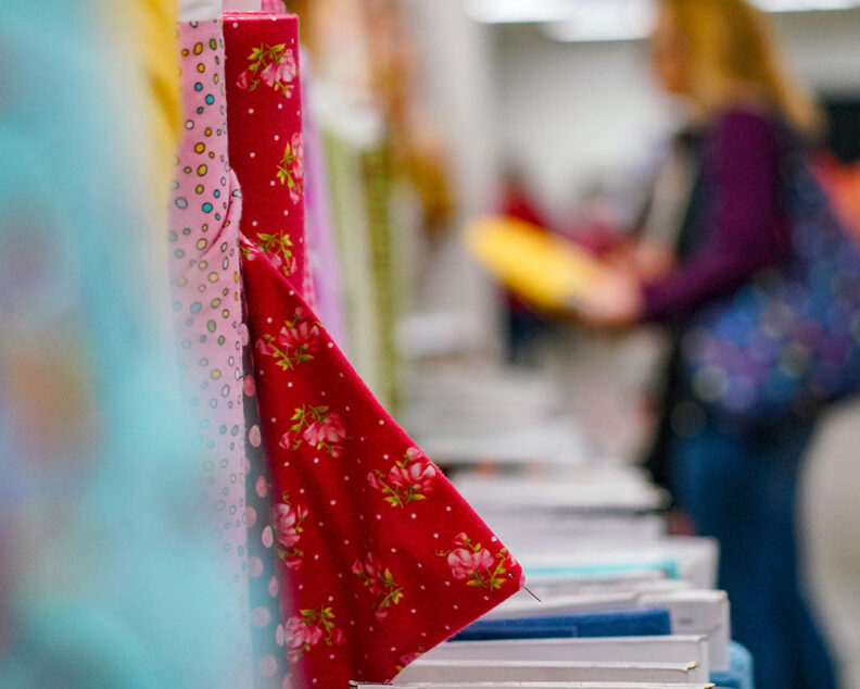 Bolts of colorful fabric. A shopper browses in the background.